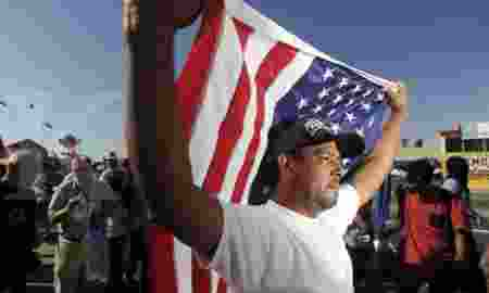 Rojas carries an American flag during a May Day demonstration in Oakland